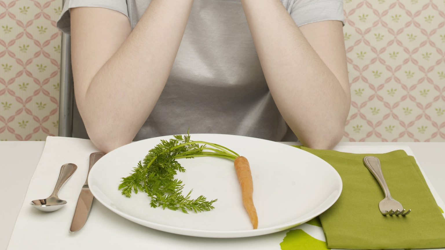 Woman looking at plate with single carrot